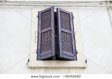 Old window with closed shutters with flowers on the window sill on the stone wall. Italian Village.