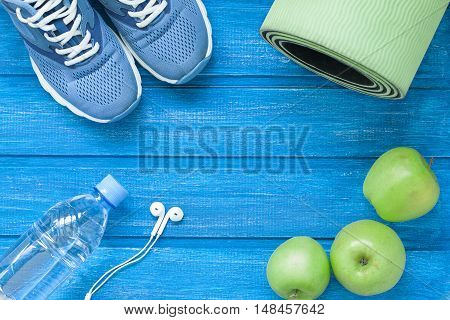 Flat lay sport shoes bottle of water mat and earphones on blue wooden background. Concept healthy lifestyle sport and diet. Selective focus.