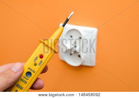 Electricity current meter turn-screw near to the socket on orange wall.