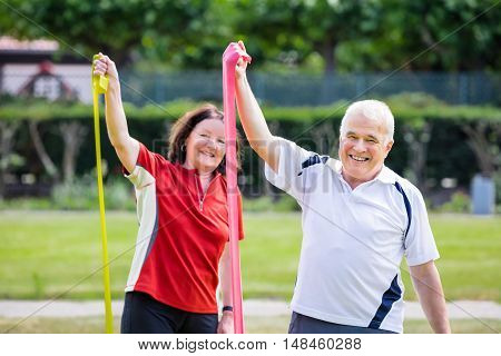 Happy Senior Couple Doing Work Out In Park