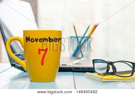 November 7th. Day 7 of month, Morning coffee yellow cup with calendar on chief workplace background. Autumn time. Empty space for text.