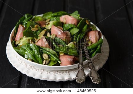 Salad with spinach avocado and pumpkin seeds salted fish