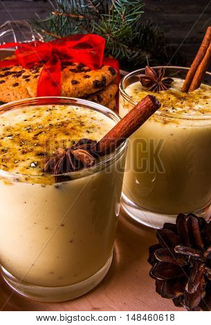Traditional Christmas drink eggnog and cookies on a wooden background surrounded by Christmas tree branches