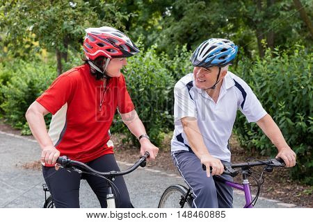Happy Senior Couple Looking At Each Other While Riding Bicycle In Park