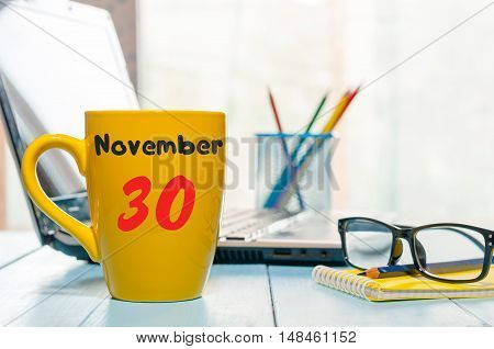 November 30th. Day 30 of month, calendar on hot coffee cup at translator or interpreter workplace background. Autumn time. Empty space for text.
