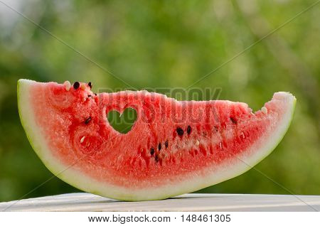 Large slice of watermelon with a heart carved into the flesh against the backdrop of greenery