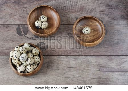Three Wooden Bowls With Quail Eggs. Rustic Wood Background, Diffused Natural Light. A Different Type