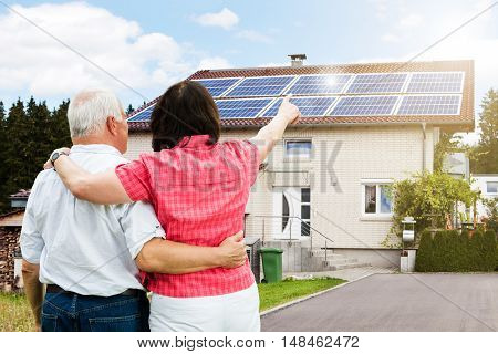 Rear View Of Senior Couple Pointing Finger In Front Of House