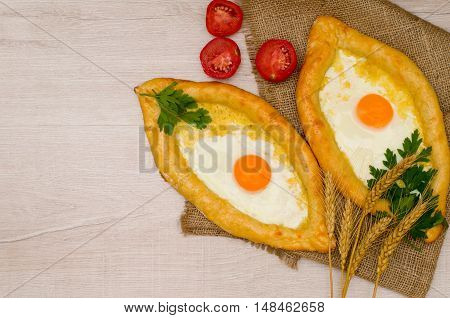 Two pie with cheese and eggs on a wooden light background tomatoes and ears