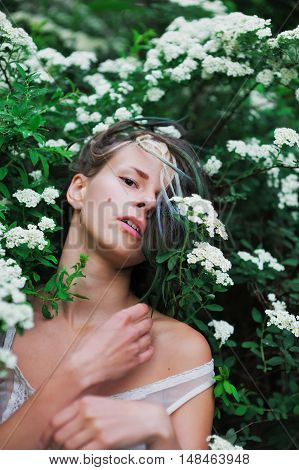 beautiful girl among green shrubs and white flowers breathe fragrance of nature