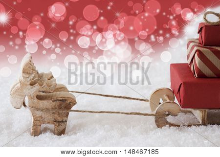 Moose Is Drawing A Sled With Red Gifts Or Presents In Snow. Christmas Card For Seasons Greetings. Red Christmassy Background With Bokeh Effect And Stars. Copy Space For Advertisement