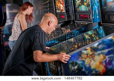 Young man playing pinball in game room