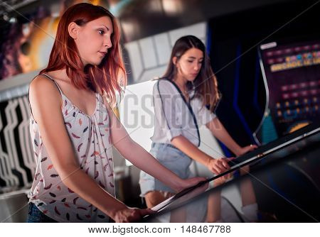 Young woman playing pinball in game room