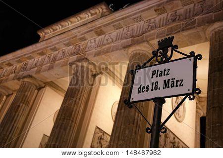 Platz des 18. Marz sign and Brandenburg gate at night in Berlin Germany