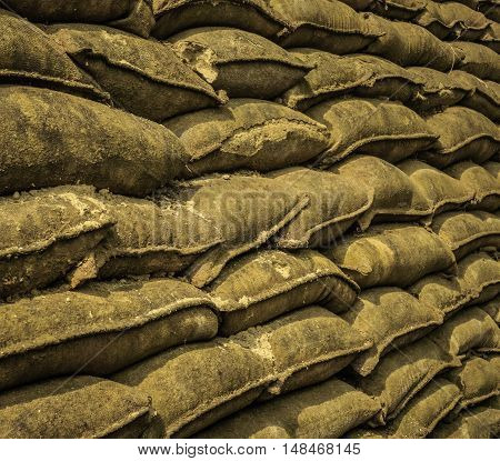 Rows of burlap sand bags piled high to form a wall.