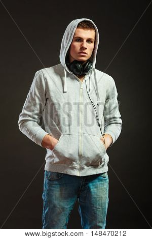 young serious hooded man teen boy with headphones listening to music black background