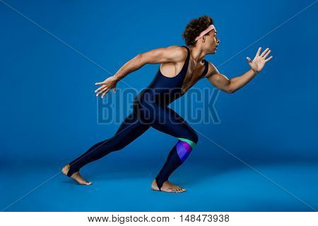 Young handsome sportive african man pretending run over blue background. Copy space.