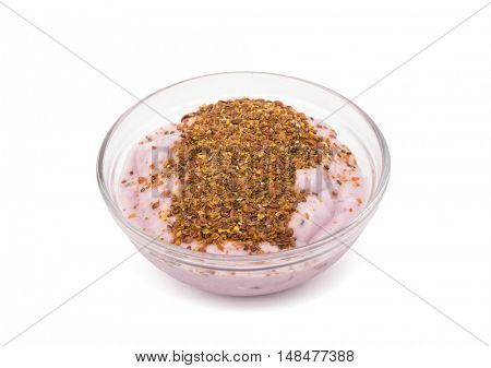 Blueberry yogurt in a glass bowl with whole Flax and ground Chia seeds on top - a nutritious and healthy breakfast - on white