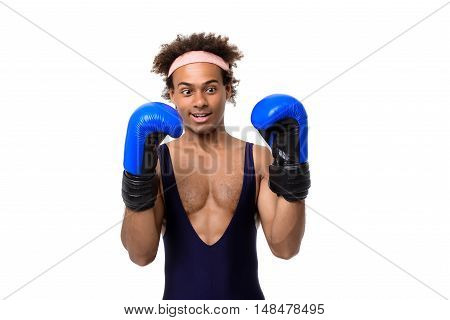 Young handsome sportive african man in boxing gloves posing over white background. Copy space.
