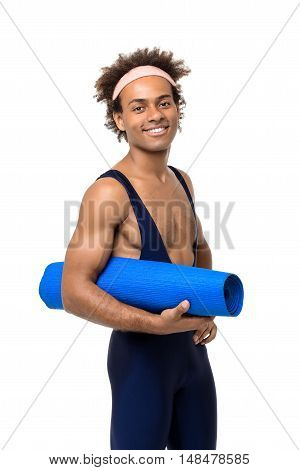 Young handsome sportive african man smiling, holding karemat over white background. Copy space.