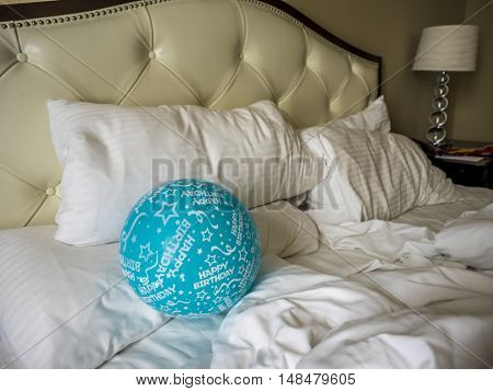 After birthday party, balloon on not made bed in the morning