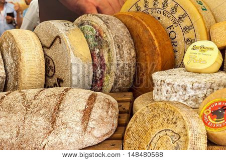 BRA, ITALY - SEPTEMBER 18, 2015: Different types of mature hard cheese on the stand. Hard cheese (granular cheese) produced by stirring and draining mixture of curd and whey and has rich tangy taste.
