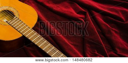Classical nylon guitar lying on red velvet textile, artistic instrument presentation.