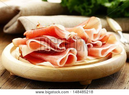 delicacy cutting ham prosciutto on wooden board