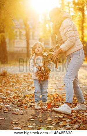 Family walk. Mother and daughter throw up fallen leaves. Autumn Park. Cute family relationships. Sunset. Warm toning. Fun.