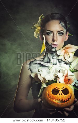 Young attractive girl with creative make-up for Halloween. She is holding a pumpkin in hand. Mysterious and frightening image of lilies. Witchcraft. Horrible.