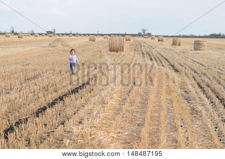 Little girl running on the field with stack of hays