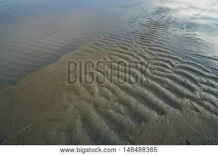 Natural sand pattern on flat sandy beach during low tide.