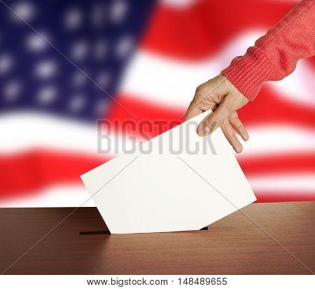 Hand with ballot and box on Flag of USA