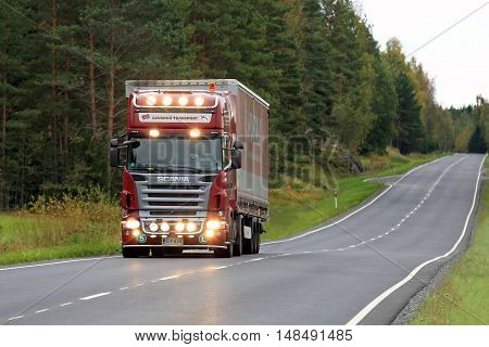 SALO, FINLAND - SEPTEMBER 17, 2016: Red Scania semi cargo truck of Savakko Transport on rural road. The driver flashes the high beam lights briefly.