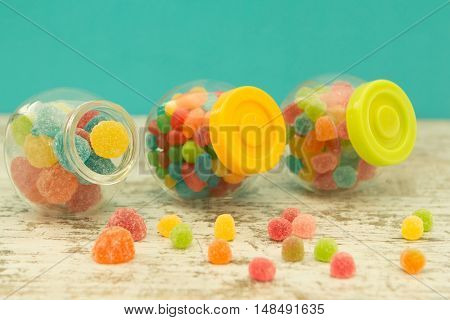Three glass jars full of jellybeans on wooden table with blue background