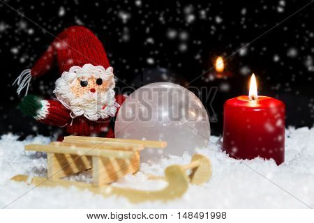 Santa Claus, A Sledge And A Candle In The Snow, Black Background With Snowfall