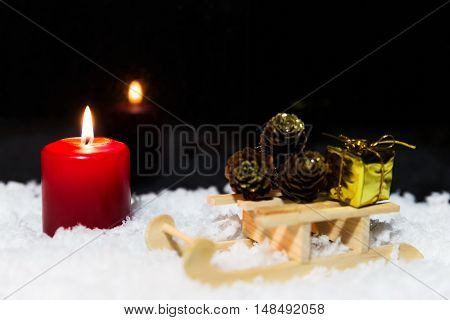 Wooden Sledge With Presents And Candle In The Snow, Black Background