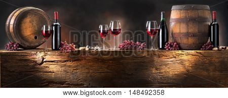 still life with red wine and barrel on old wood