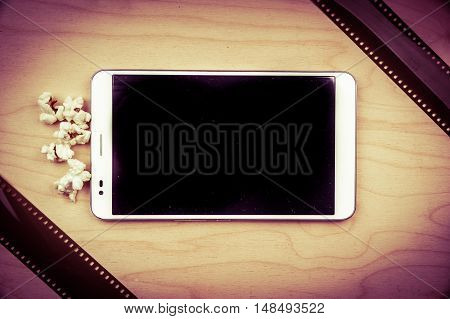 Tablet pc on wood with attributes of cinema. Visual metaphor for internet content - films and media on a mobile device.