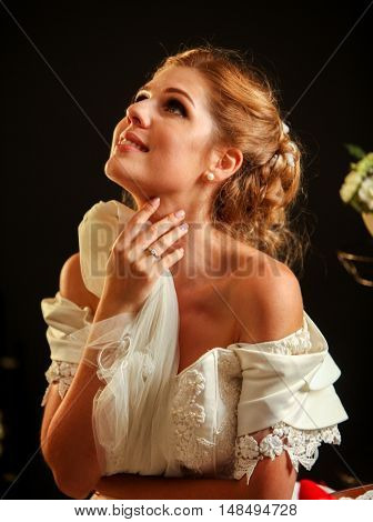 Happy girl in wedding dress looks up. Bride wearing white wedding dress on black background.