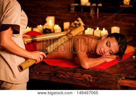 Bamboo back massage. Young woman lying on wooden spa bed have bamboo massage therapy sticks. Bamboo massage in spa salon. Girl on candles background in massage spa salon.