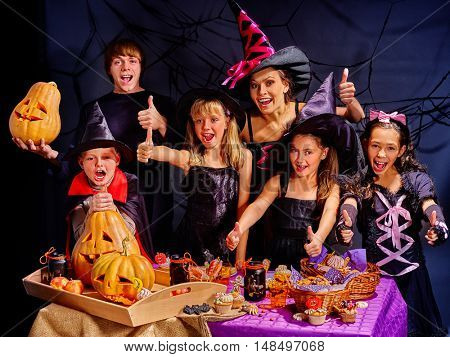 Children on Halloween party making carved pumpkin. Halloween on black background.