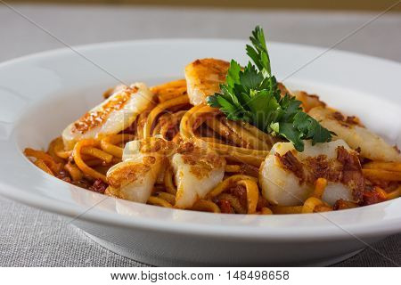 Pasta (spaghetti) With Scallops And Tomato Sauce Is On The Plate