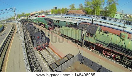 Old trains on the tracks at a railway station on a sunny day, aerial view