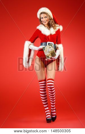 Full length portrait of a beautiful smiling Christmas girl with a gift box. Merry red background.
