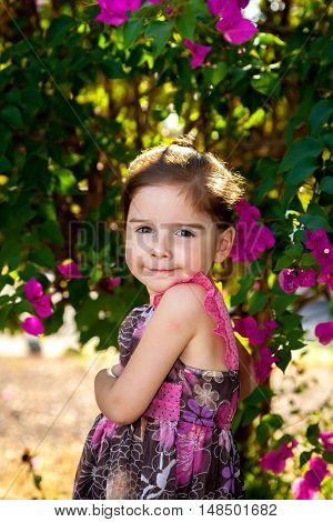 Cute girl with body turned to the side in a sassy pose. She has a smug look on her face. She has a brown and pink dress and is outdoors.
