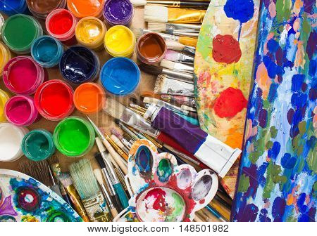 Colorful paints, brushes, palette on the wooden background. The workplace of the artist. Banner for the school.