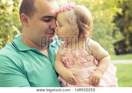 Portrait of a dad holding his little daughter. Close-up