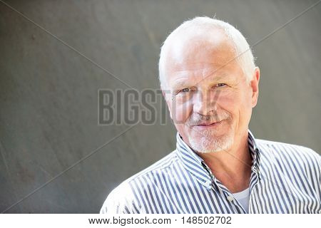 Senior man in front of a grey wall