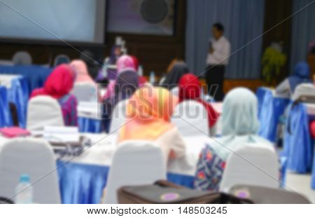focus blurred of university students. sitting in a lecture room with a teacher in front of the class with white projector slide screen with copy space.